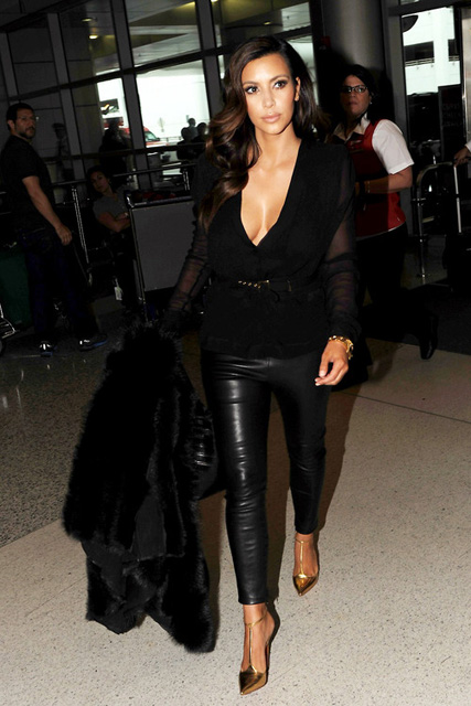 Reality star Kim Kardashian makes her way through the airport in Miami where she posed with fans before heading through security